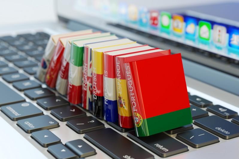 A selection of translation books on a laptop keyboard