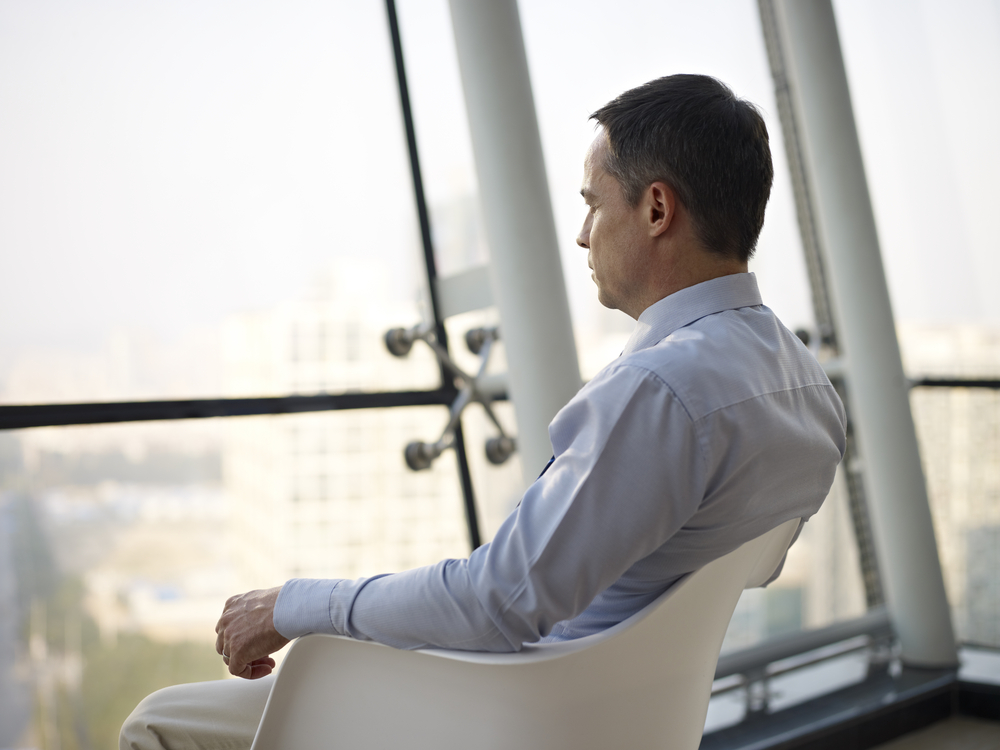 Man looking out of window reflecting