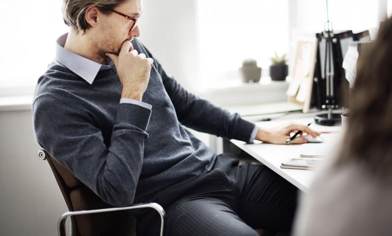 Businessman sat at desk thinking pensively