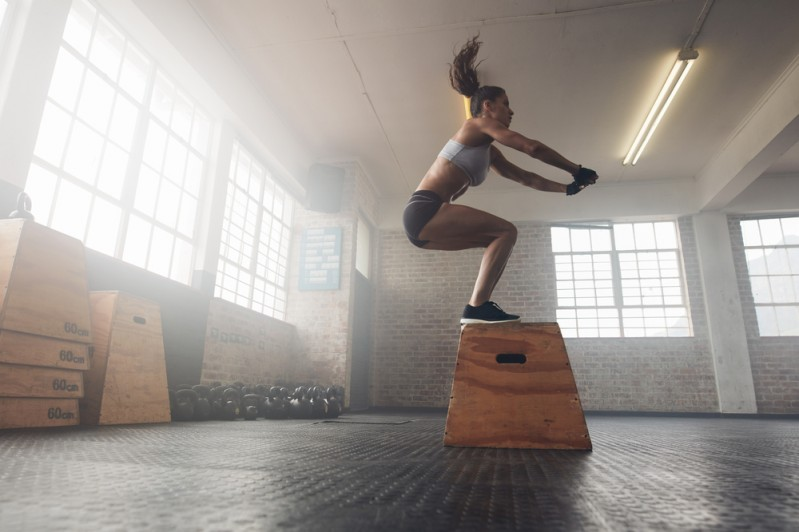 A woman demonstrating an agile approach by jumping onto a box