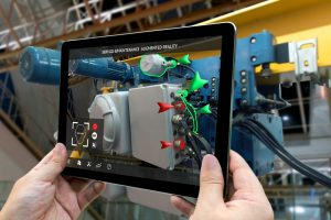 Hands holding tablet that demonstrates AR learning for engine repair