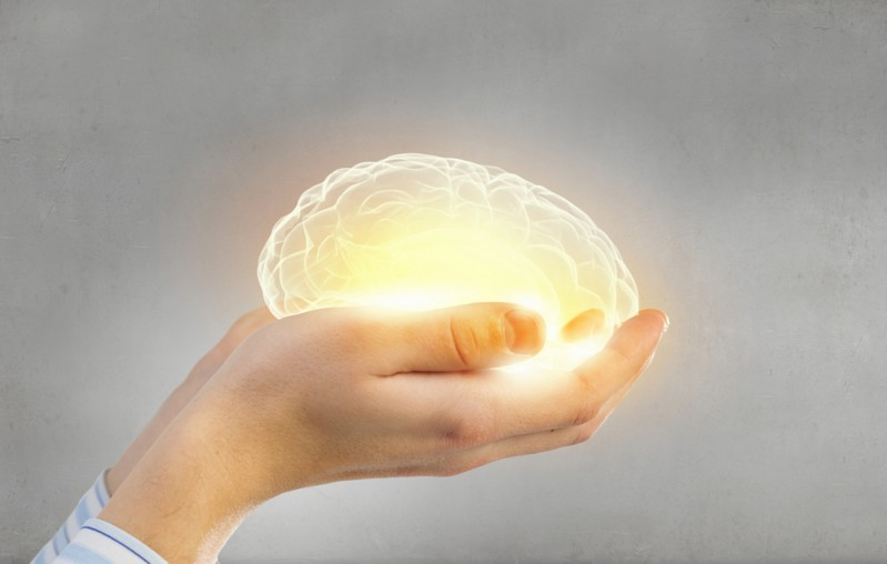 hands holding warm glowing brain representing mental health care to to help relearn mental health