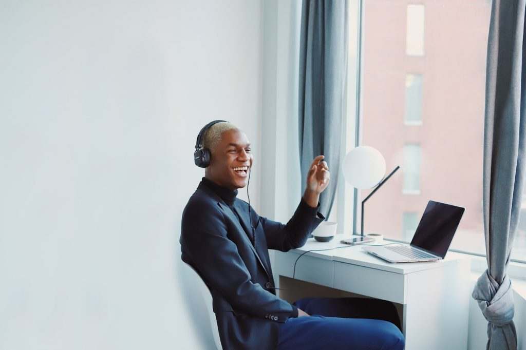 Guy sitting at desk with headset lauughing