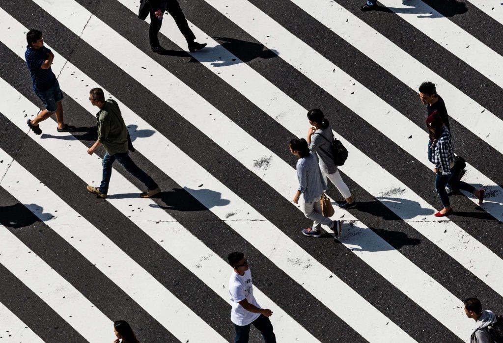 people walking over crosswalk