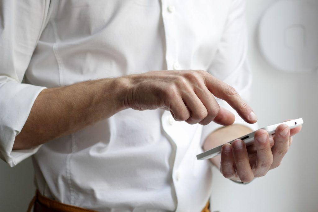 white man in white shirt holding phone