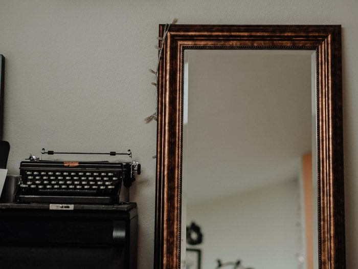 Typewriter and mirror leaning against wall