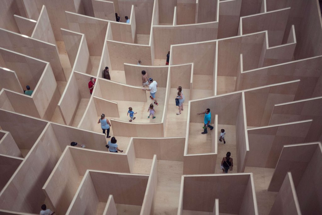 people walk through a maze with overconfidence