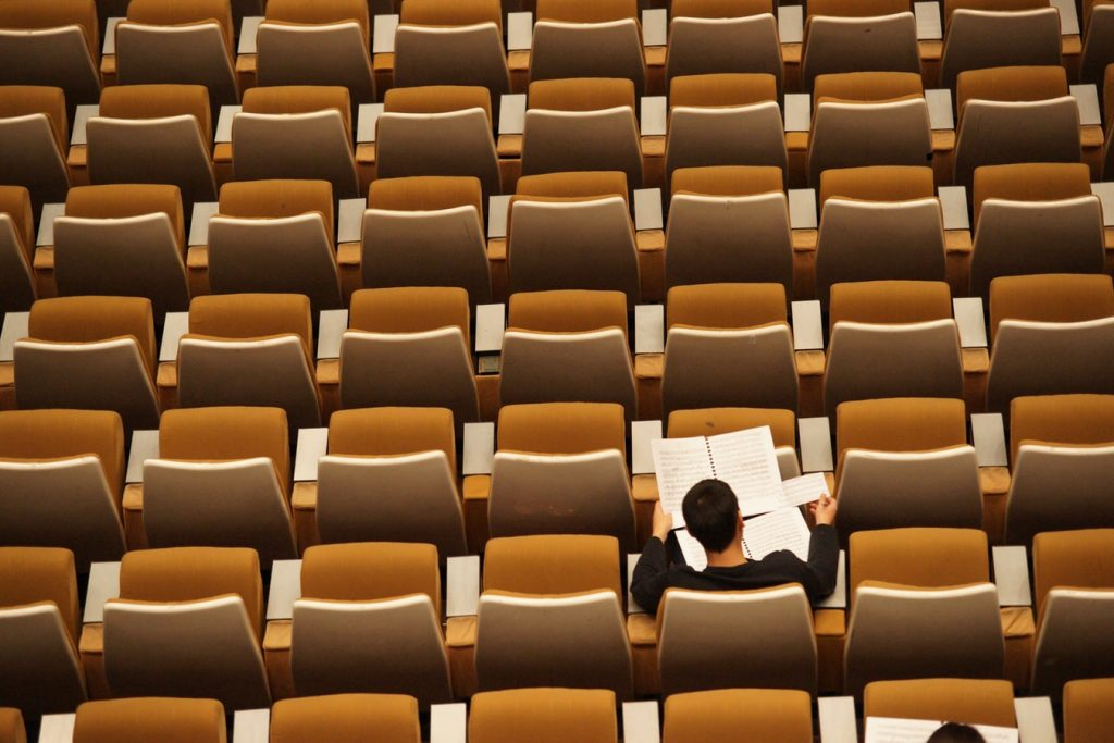 person sitting alone in auditorium, representing opposite of social learning
